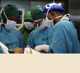 Dr. Greenfield, with Tanzanian residents, attends to a patient in the operating room.