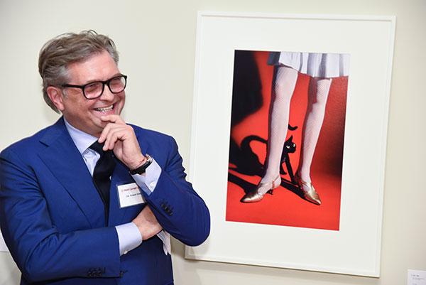 Dr. Roger Härtl in front of a whimsical Elliott Erwitt photo