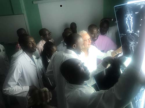 Dr. Stieg, with Dr. Cisse at his left, reviews imaging from a patient who needs surgery